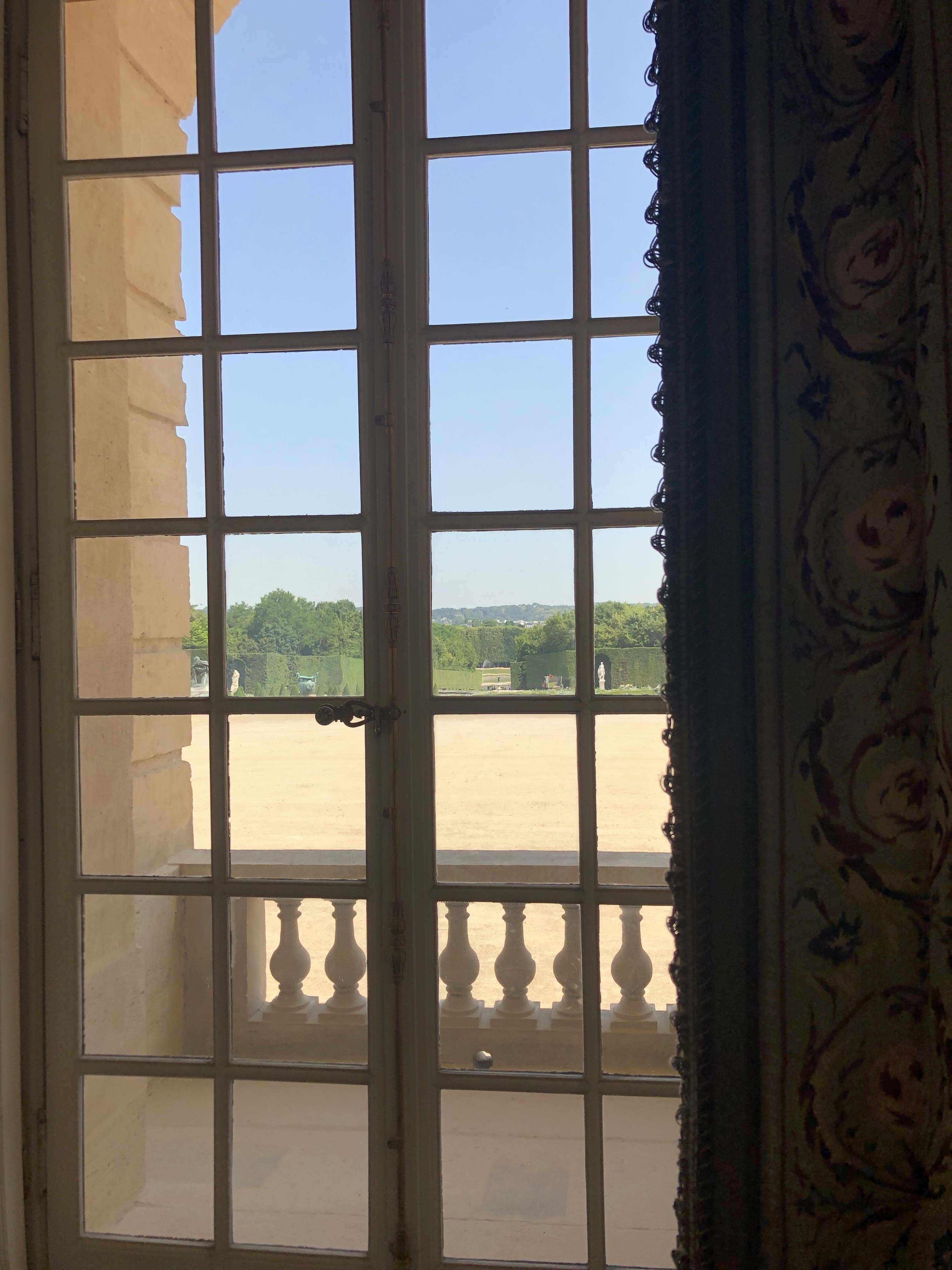 View through a window of sunny grounds at the palace of versailles