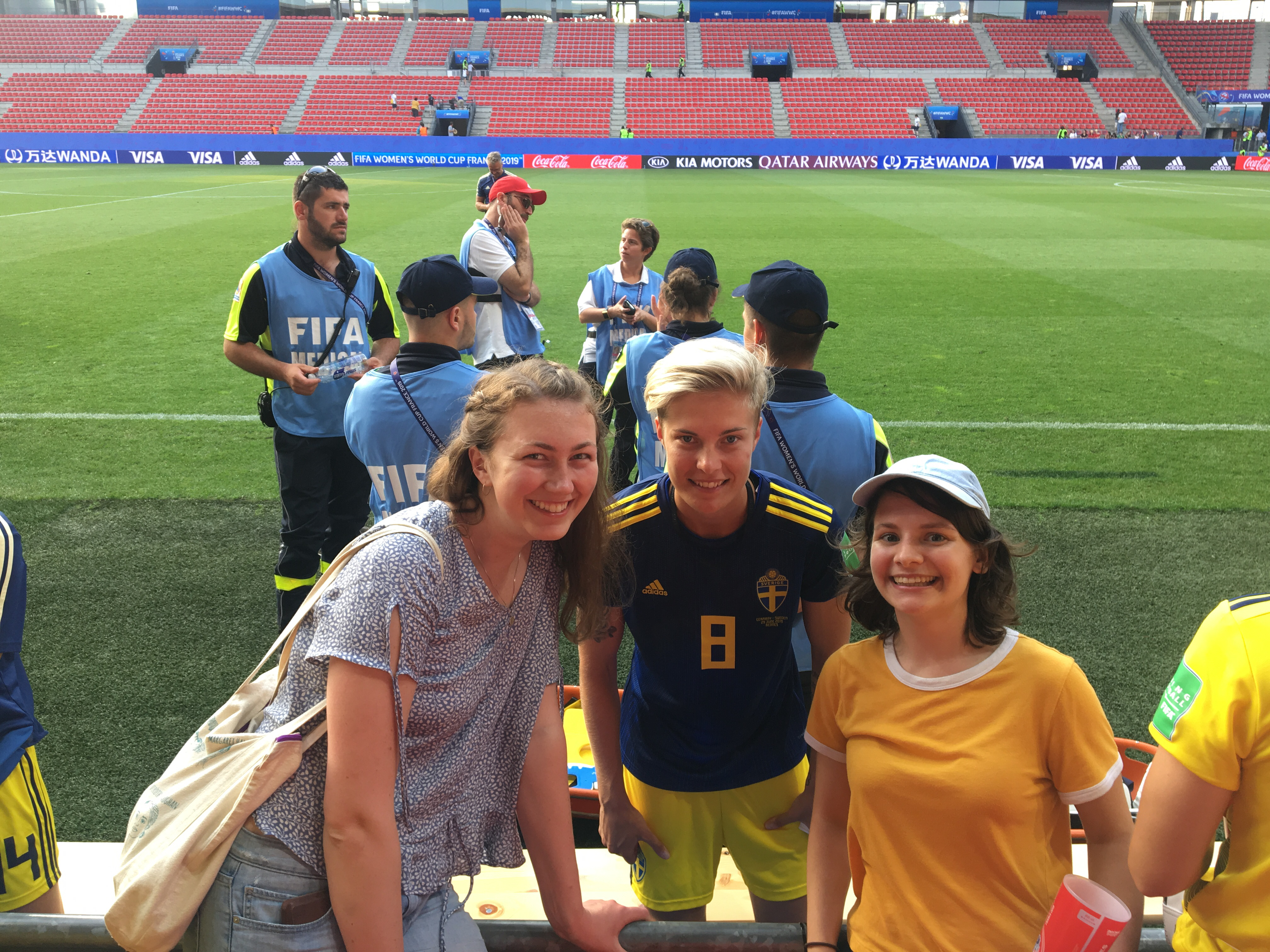 A Swedish soccer player and two fans next to the field